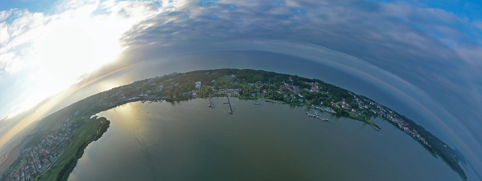 Drone Aerial 360 Degree Panoramic Curved View on Touristic City Located on Spit between Sea and Lake stock photo