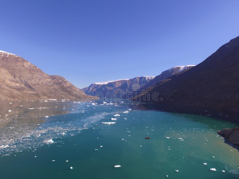 Drone aerial image of icebergs and turbid glacial runoff in a narrow fjord in Northeast Greenland royalty free stock photos