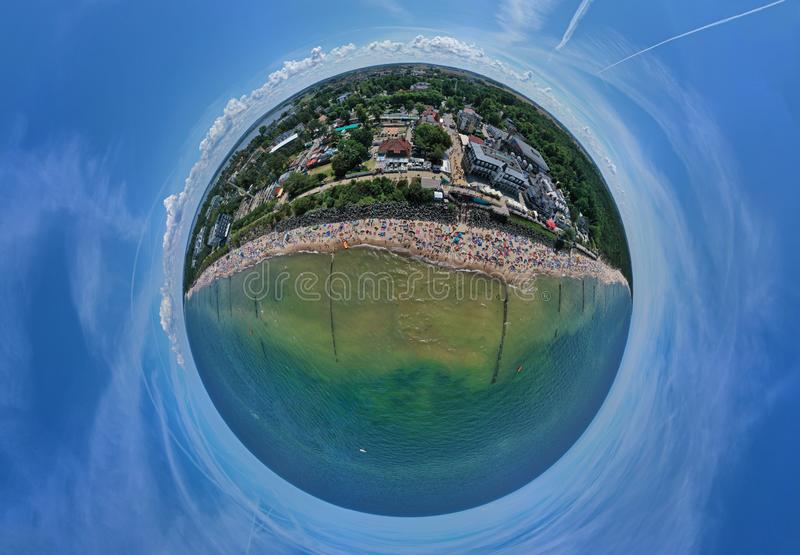 Drone aerial panoramic 360 degree view on sunny beach with sunbathers with windbreaks and towels at sea in touristic city royalty free stock photos