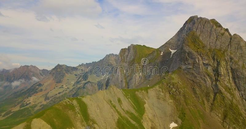 Drone aerial view of huge mountain scenery during summer with green grass and clouds. Nature, peace, tranquility, peaks, blue, sky, bids, eye, forestation stock photos