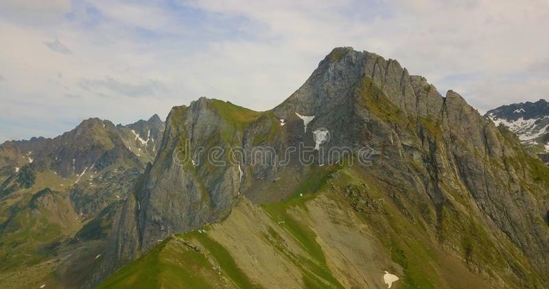 Drone aerial view of huge mountain scenery during summer with green grass and clouds. Nature, peace, tranquility, peaks, blue, sky, bids, eye, forestation royalty free stock photos