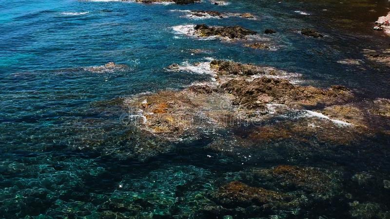 Drone aerial view of the ocean with rocks and waves. White, soft, clouds, blue, sky, above, fluffy, summer, weather, climate, hot, warm, young, attractive royalty free stock photo