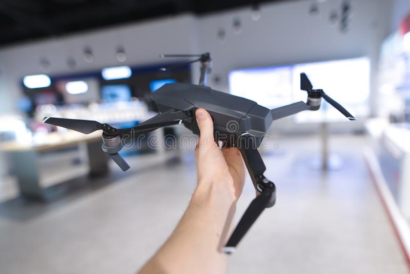 Drone on the background of the store. Man holds a drone indoors.  royalty free stock image