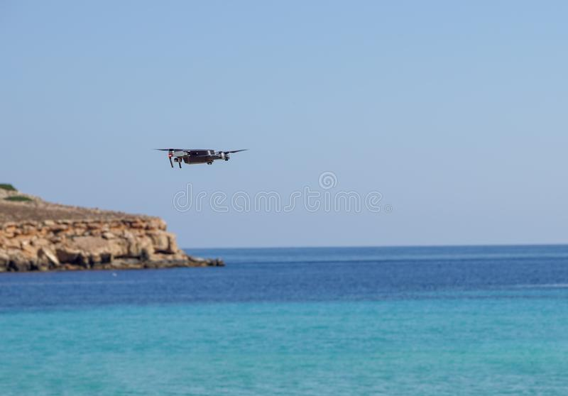 Drone being operated at the sea shore. summer vacation flying drone on beach. Focus on drone, with sea at background. stock images