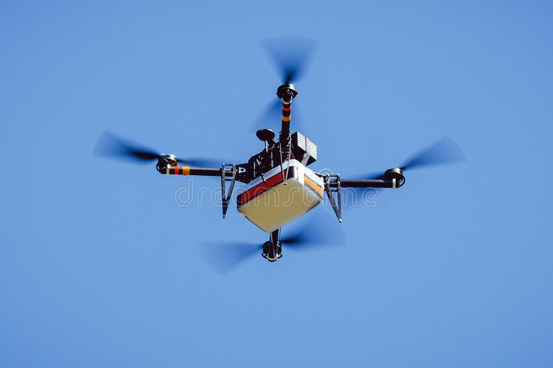 Drone carrying package. Quadcopter delivery flight cargo royalty free stock photography