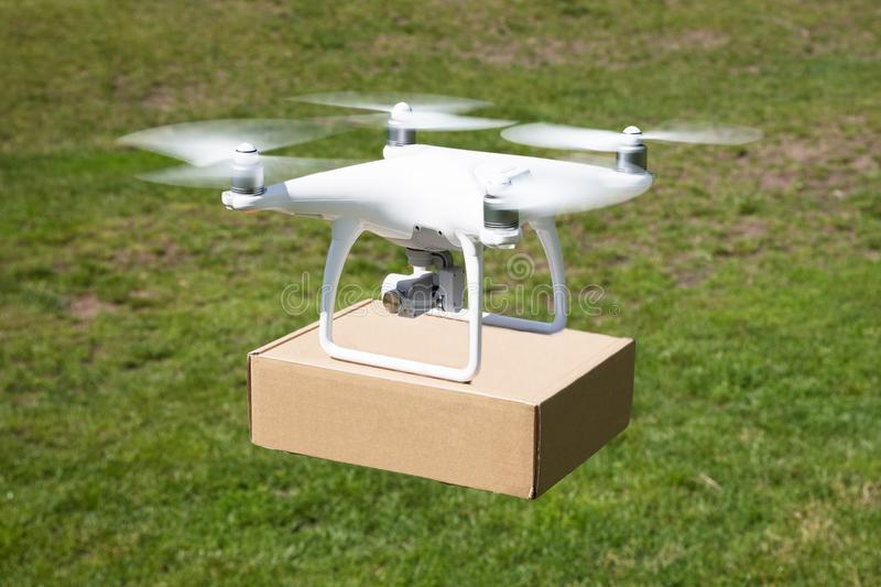 Drone carrying parcel over grassy field royalty free stock photography