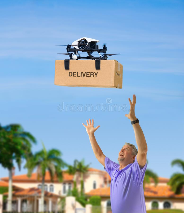 Drone delivering box package on delivery flight to a happy waiting man with outstretched arms stock image
