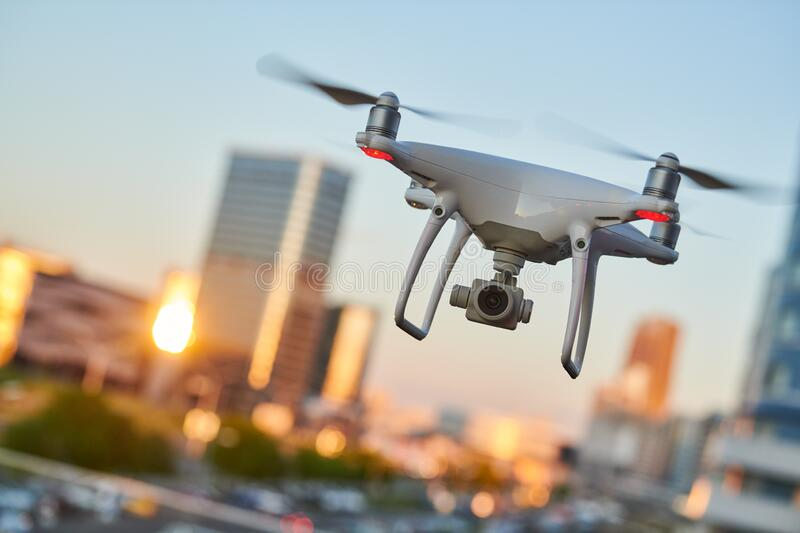 Drone with digital camera flying at city street stock images