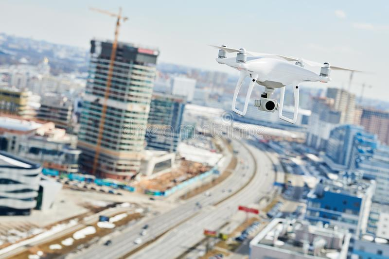 Drone with digital camera hovering over city. Drone with digital camera flying or hovering in blue sky over the city royalty free stock photo