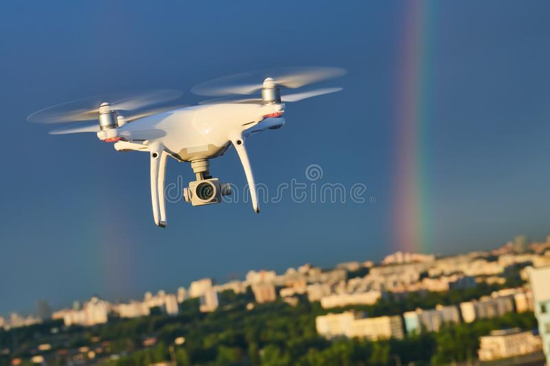 Drone flying over city with digital camera at rainbow royalty free stock photography