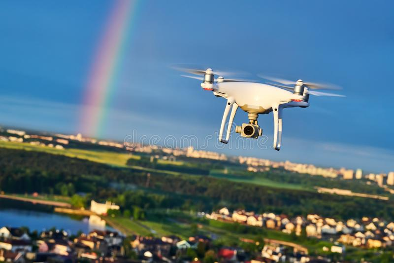 Drone flying over city with digital camera at rainbow stock images