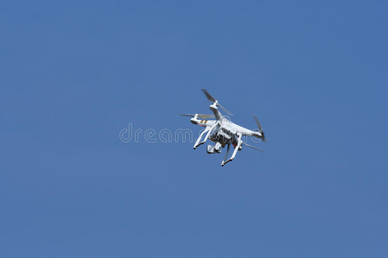 Drone with digital camera flying and hovering in the blue sky. Drone quad copter with digital camera flying and hovering in the blue sky royalty free stock photo