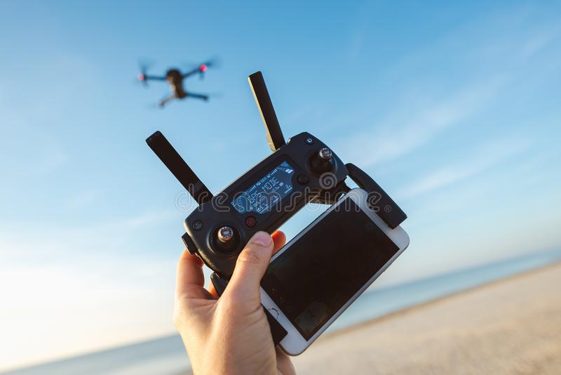 Drone DJI Mavic Pro and remote controller. Man hand holding remote controller and using quad copter on natural background royalty free stock photography