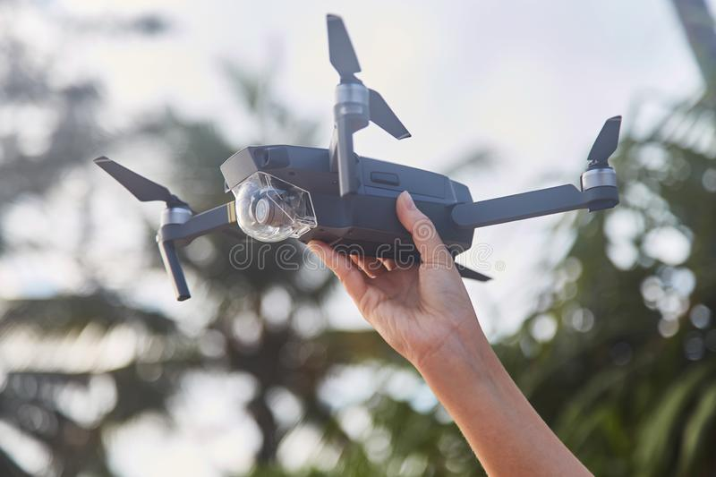 Drone in the female hand. Close-up. Girl launches drone. stock photography