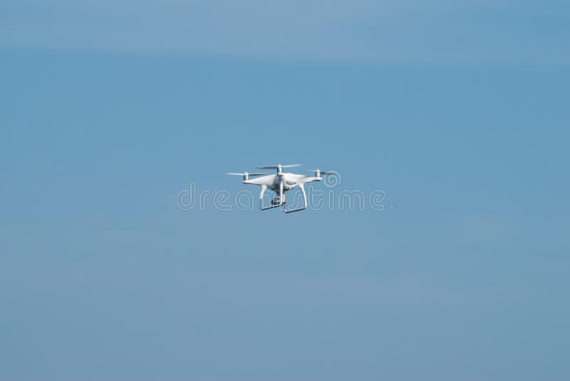Drone flying against the blue sky,. Quadcopter in the sky, white quadcopter shoots stock photo