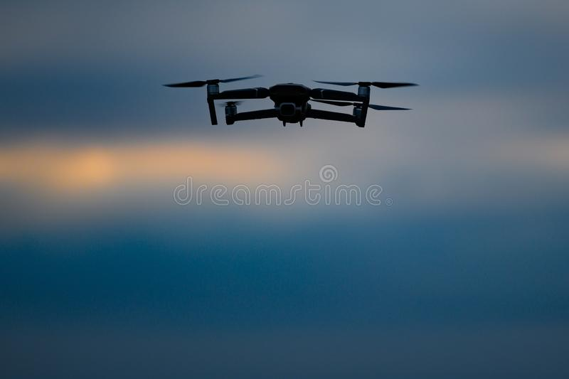 Drone flying on dark evening or night sky stock photography