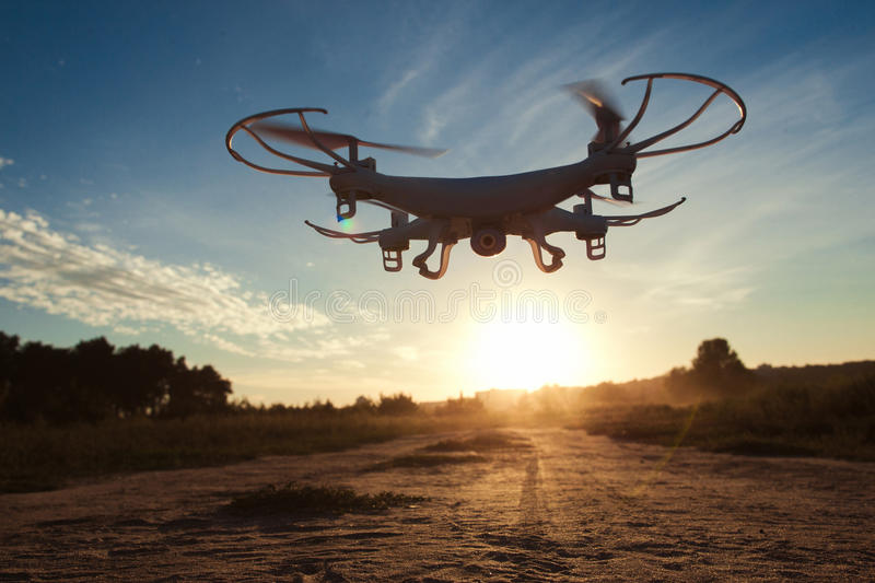 Drone flying outdoor in evening, sunset background. Quadrocopter recording video of environment. Work, innovation, modern technologies, leisure concept royalty free stock image