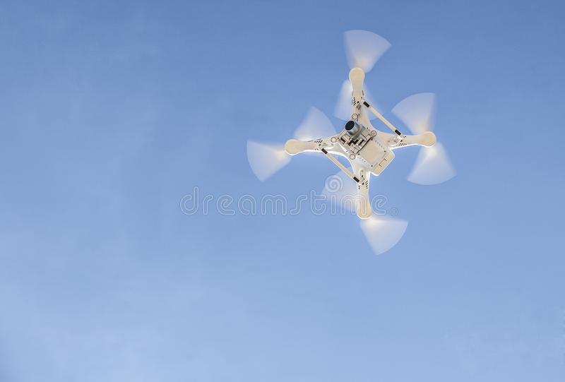 Drone flying over with camera against blue sky stock photo