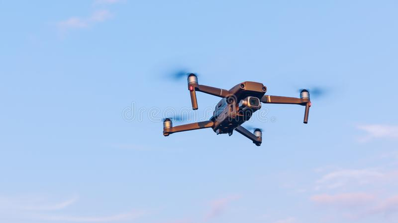 Drone flying over landscape. UAV drone copter flying with digital camera. Drone flying overhead in cloudy blue sky. Quad copter is stock photos