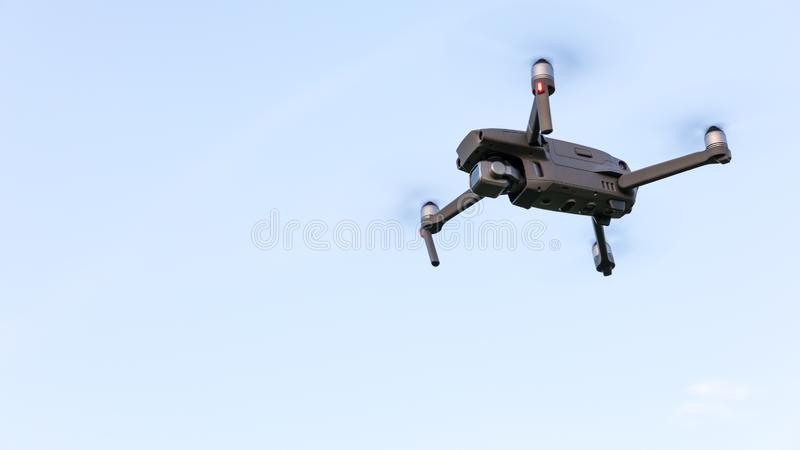 Drone flying over landscape. UAV drone copter flying with digital camera. Drone flying overhead in cloudy blue sky. Quad copter is stock image