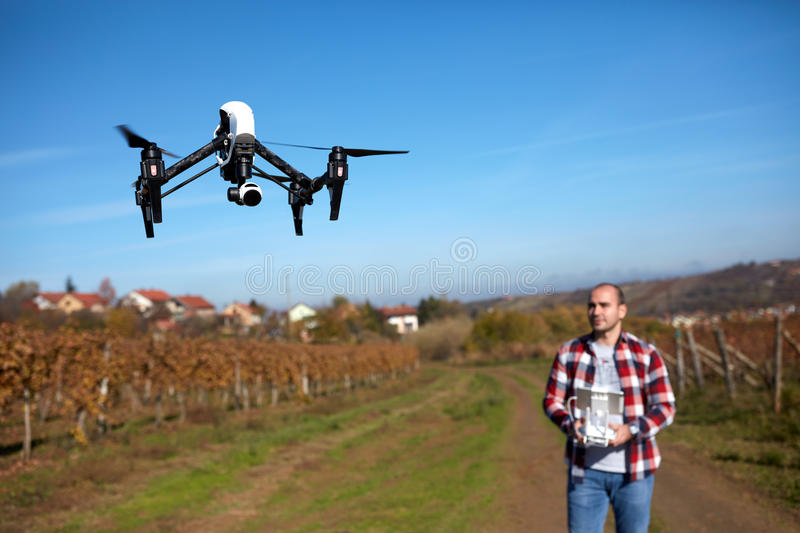 Drone flying over vineyard. Modern drone flying over vineyard navigated by male royalty free stock images