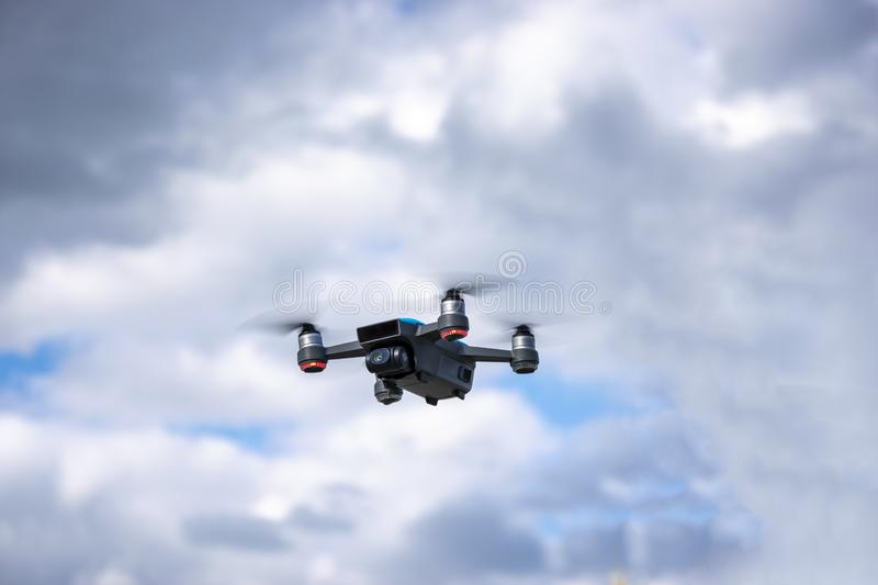 Drone flying overhead in cloudy blue sky stock photo