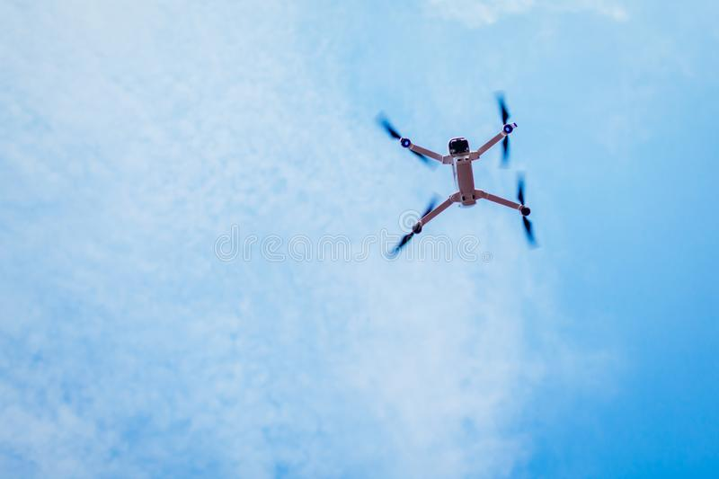 Drone flying in sky. Copter low angle view. Aerial video shooting. Recording footage with aircraft stock image