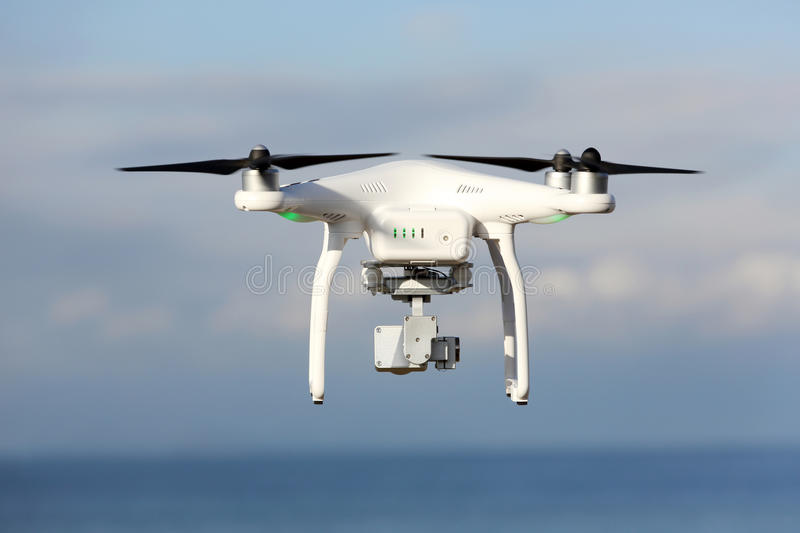 Drone flying in the sky. KAGAWA, JAPAN - DECEMBER 15, 2016: White remote controlled Drone Dji Phantom 3 equipped with high resolution video camera hovering in stock images