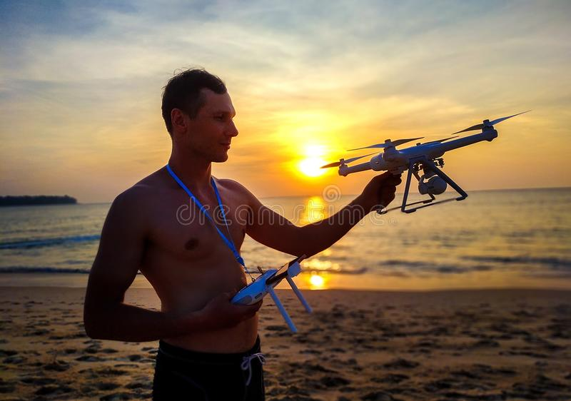 Drone flying at sunset over the sea. Man landing the drone frome the air. Sunset photo frome the air. stock photo