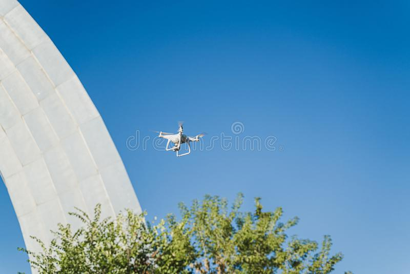 Drone is flying under the city in blue sky. Uncrewed aerial vehicle is making photo and film video at the remote command. Of the pilot. Horizontal image royalty free stock image