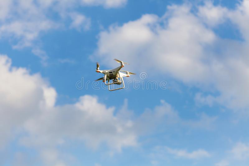 Drone hovering against blue cloudy sky. Drone hovering against blue sky with some clouds in background royalty free stock photography