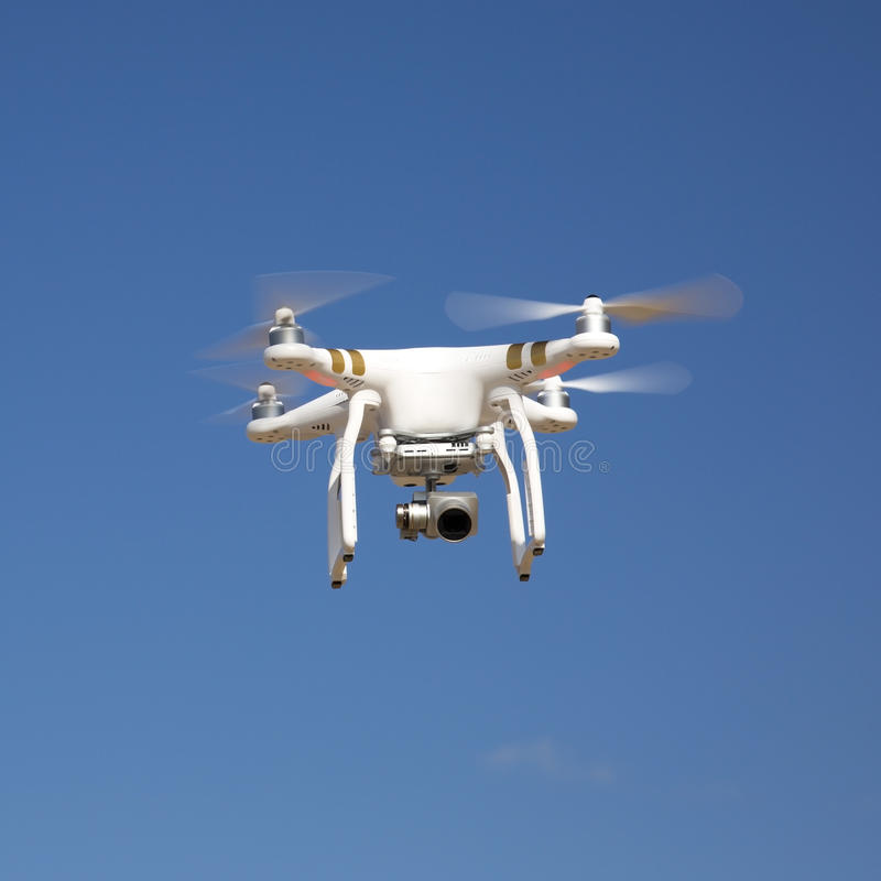 Drone hovering against blue sky on sunny day stock image