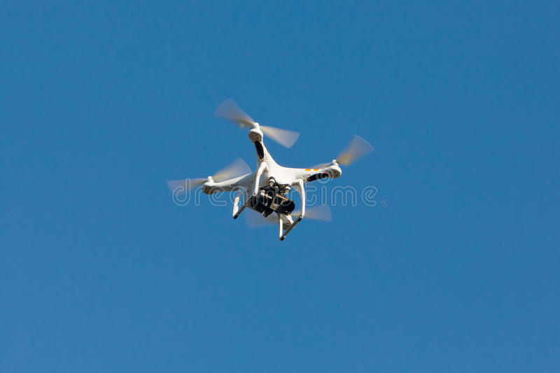 Drone hovering on the blue sky. royalty free stock image