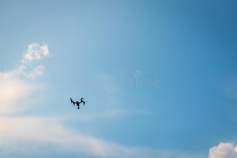 Drone hovering in a blue sky. Drone hovering in a bright blue sky stock image