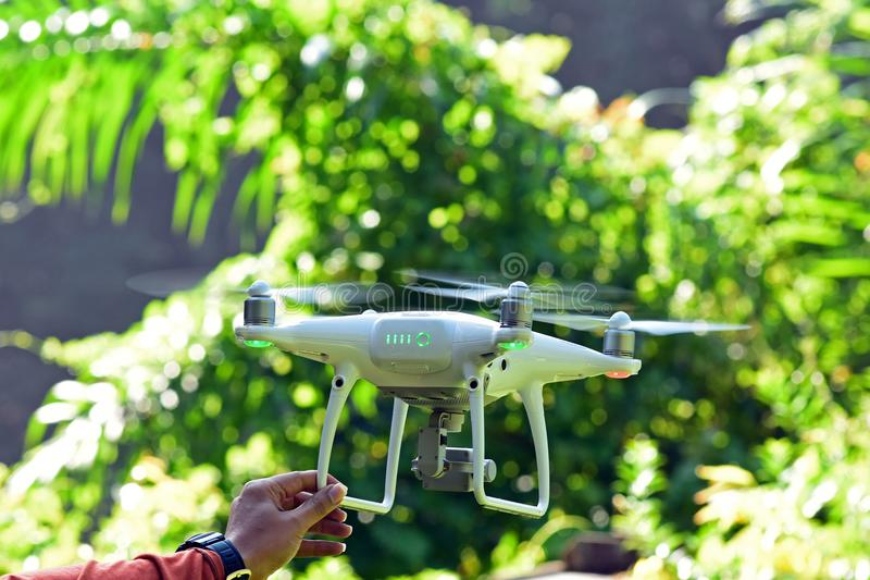 Drone hovering on man hand with green bokeh background. Drone hovering on man hand with green nature bokeh background royalty free stock photography