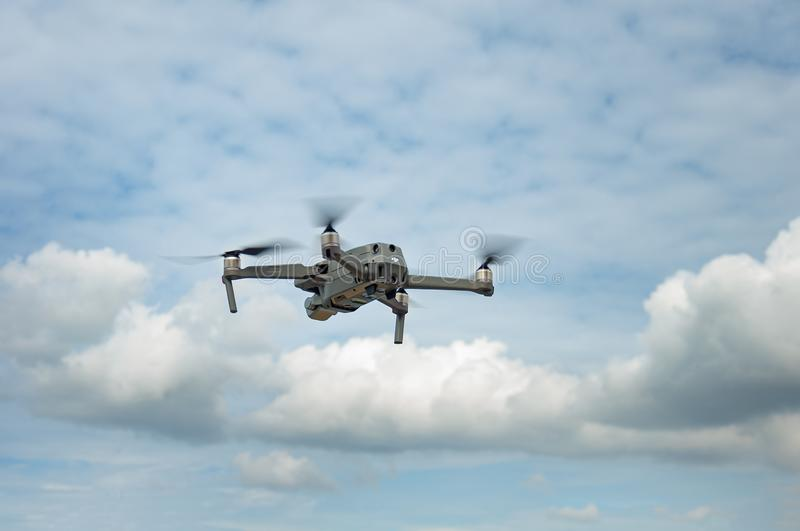 Flying drone with camera in the cloudy blue sky. stock photo