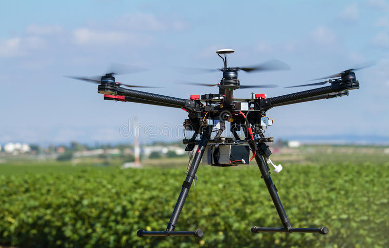 Drone hovering over green field royalty free stock photography