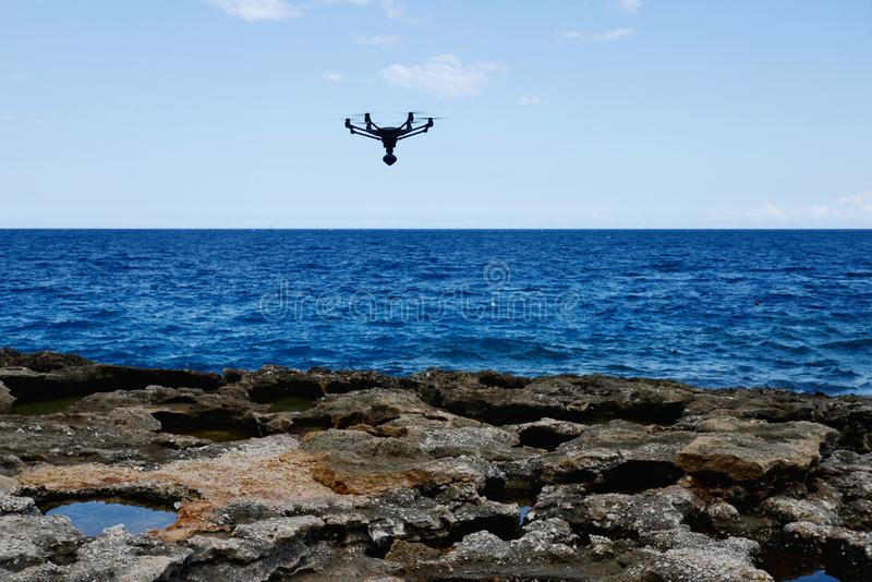 Drone hovering over sea. Technology stock image