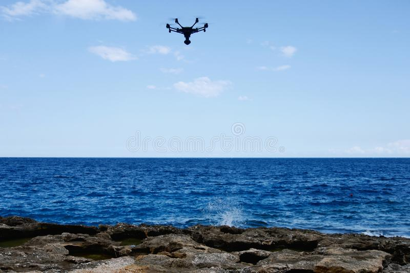 Drone hovering over sea. Technology stock photo