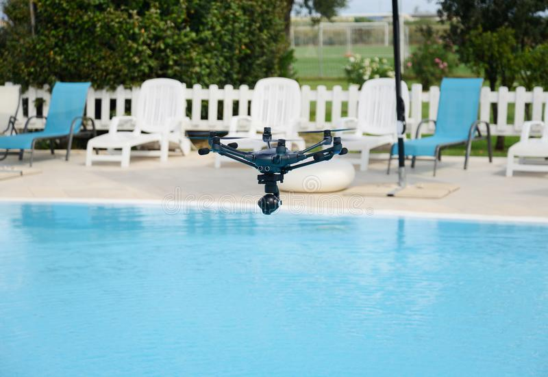 Drone hovering over swimming pool royalty free stock image