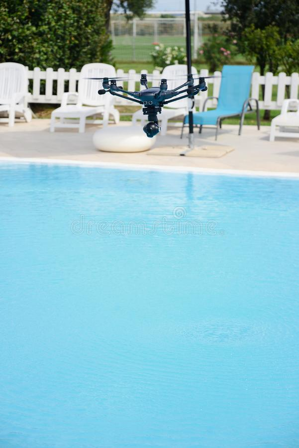 Drone hovering over swimming pool. Technology stock photos