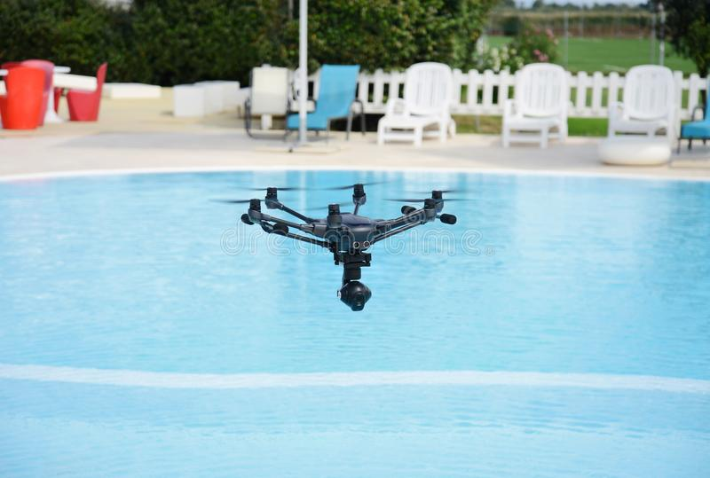 Drone hovering over swimming pool. Technology royalty free stock photo
