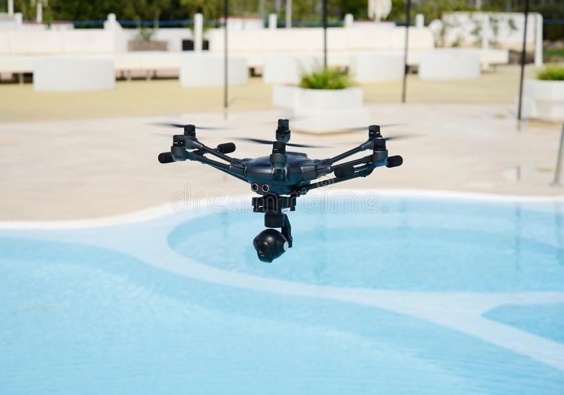 Drone hovering over swimming pool. Technology stock images