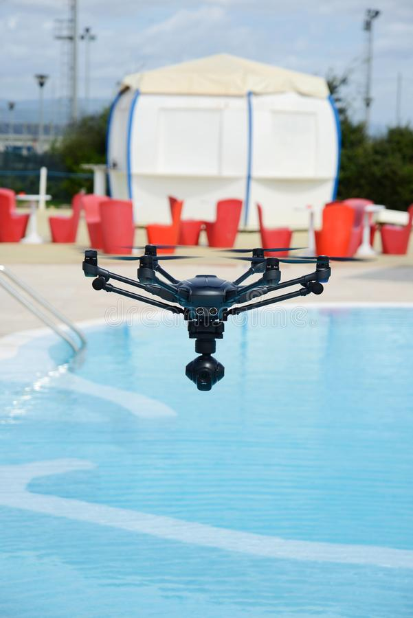 Drone hovering over swimming pool stock image
