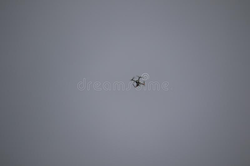A drone hovering in the sky. A drone hovering in the grey sky, air, aviation, flight, fly, high, outdoor, propellers, wing stock photography