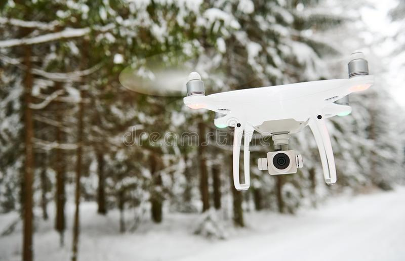 Drone hovering in winter forest. Drone with digital camera hovering in winter snowy forest stock images
