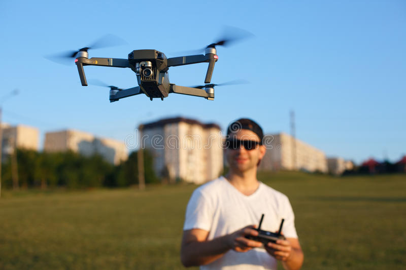 Drone hovers in front of man with remote controller in his hands. Quadcopter flies near pilot. Guy taking aerial photos. And videos stock image