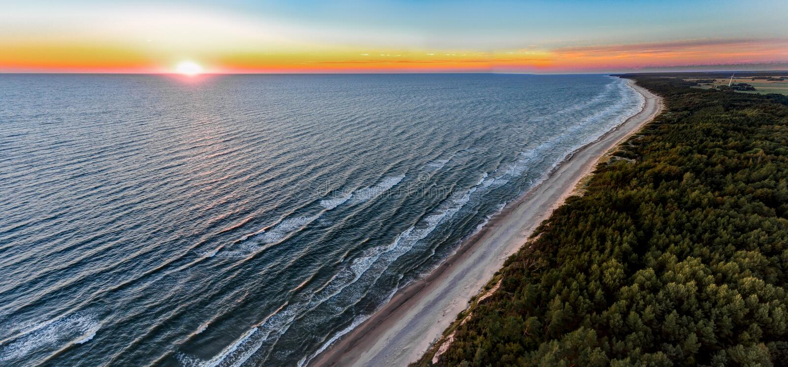 Drone image. aerial view of red sunset in the sea beach. shore line. baltic sea at dust - vintage retro look royalty free stock images