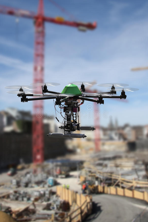 Drone construction. Octocopter drone fitted with a camera flying over a construction site