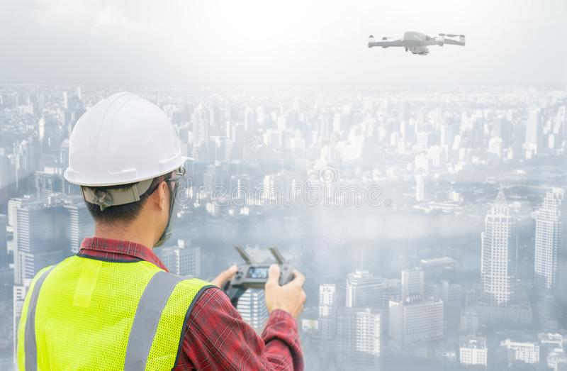 Drone operated by construction worker on building site. Construction worker piloting drone at building site with cityscape backgro stock photography